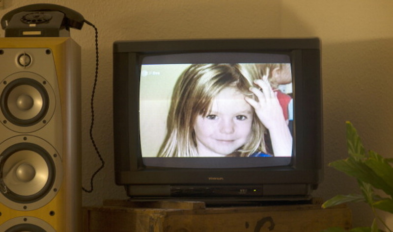 Photograph of missing Madeleine McCann on TV screen.