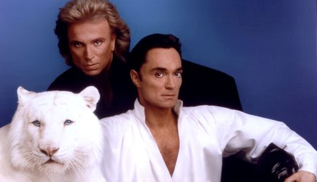 Siegfried Fischbacher and Roy Horn posing with a white tiger