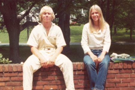 John Moxley and Martha Moxley sitting on a brick wall.